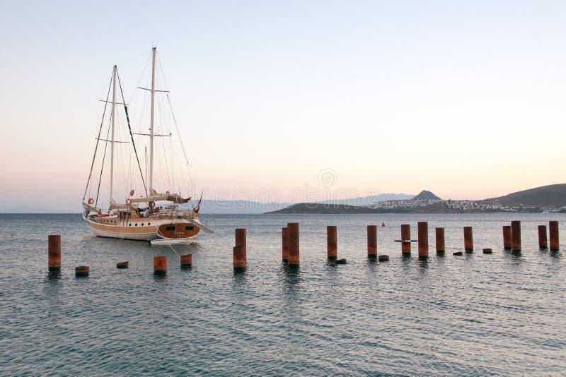 Yate del barco de navegación, el océano y la puesta del sol Puerto de Bodrum, Turquía Rompeolas con los posts de acero fotos de archivo libres de regalías