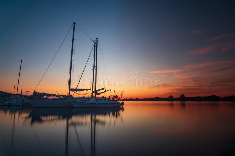 Yate del barco de vela de la salida del sol de la puesta del sol en el muelle fotografía de archivo libre de regalías