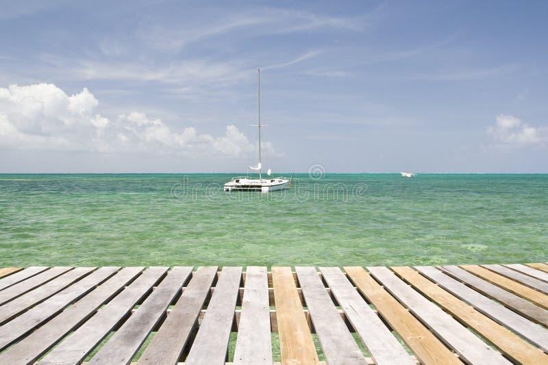 Yate delante del embarcadero de madera, calafate de Caye foto de archivo