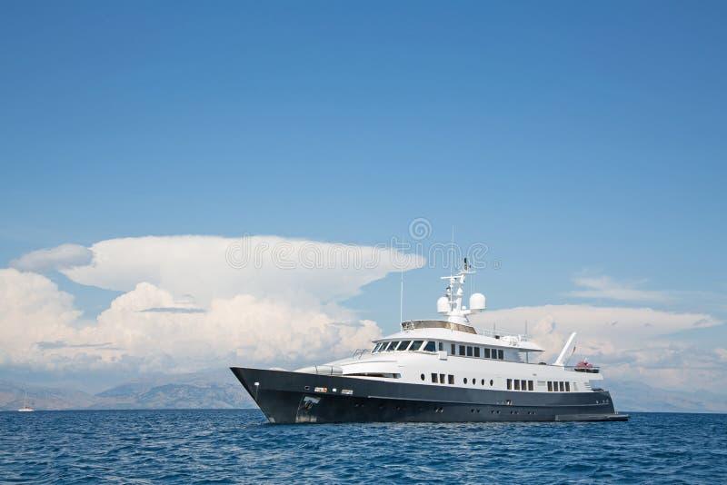 Yate estupendo o mega grande de lujo del motor en el mar azul foto de archivo libre de regalías