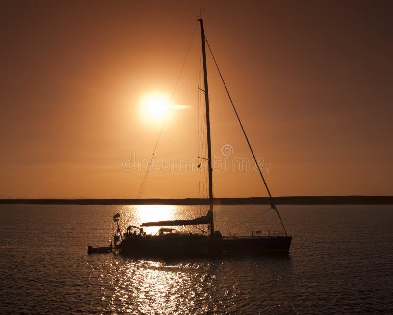 Yate grande de la navegación en puesta del sol imagen de archivo