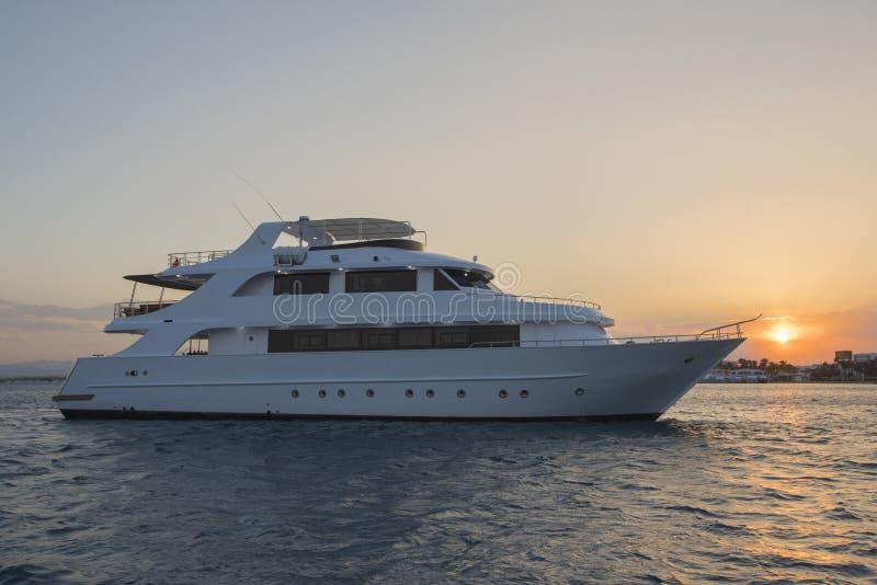 Yate privado de lujo del motor en el mar tropcial en la puesta del sol fotos de archivo