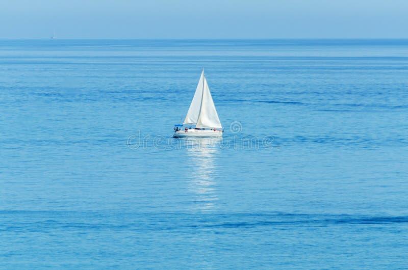 Yate que navega el mar, el cielo claro y el agua azul, deporte recreativo, resto activo imagenes de archivo