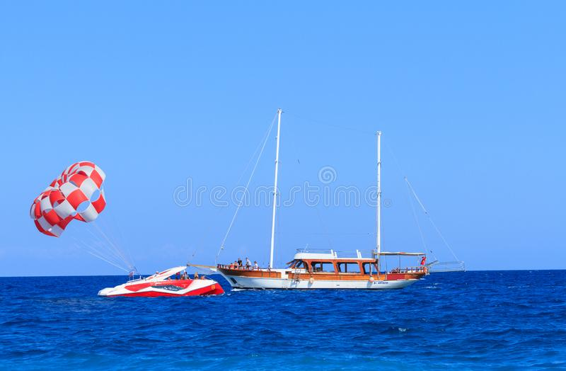 Yate y powerboat con el paracaídas en el mar en Antalya imagen de archivo libre de regalías