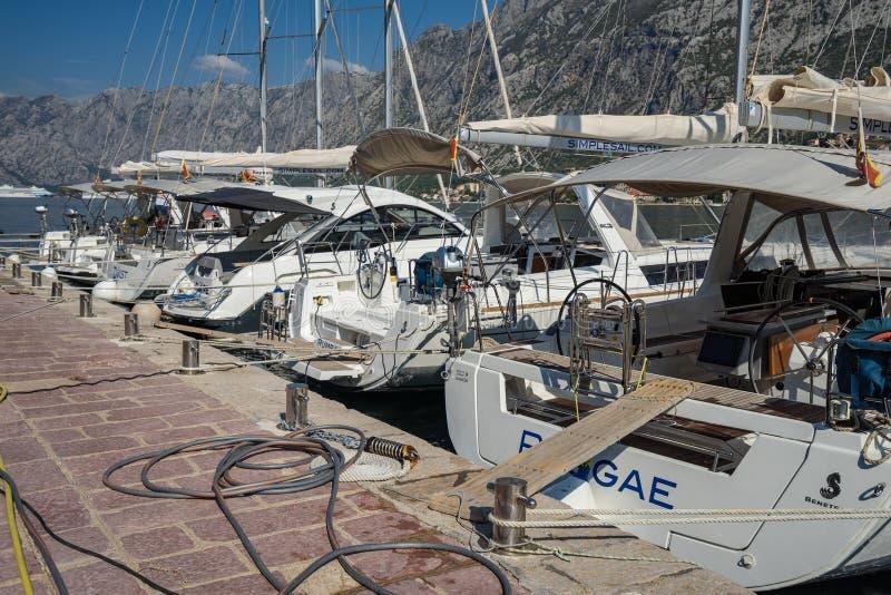 Yates blancos grandes y pequeños, barcos de motor y barcos que reman amarrados en el embarcadero en la costa fotografía de archivo libre de regalías