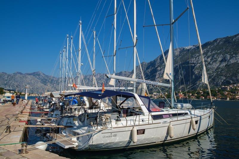 Yates blancos grandes y pequeños, barcos de motor y barcos que reman amarrados en el embarcadero en la orilla del mar fotografía de archivo libre de regalías