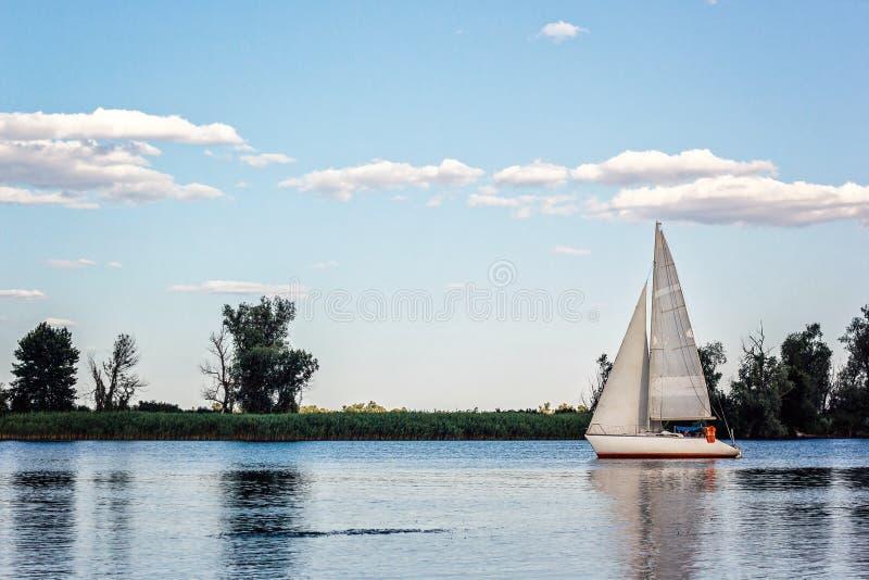 Yates en la regata de la navegación La nave hermosa navega con las velas blancas en el río de Dnieper en un fondo del cielo azul  imagen de archivo libre de regalías