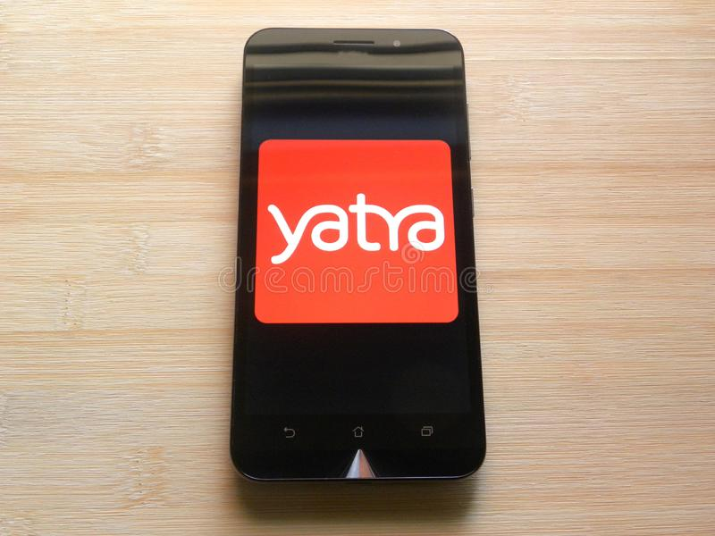 Yatra app on mobile phone. Yatra app on smartphone kept on wooden table royalty free stock photography