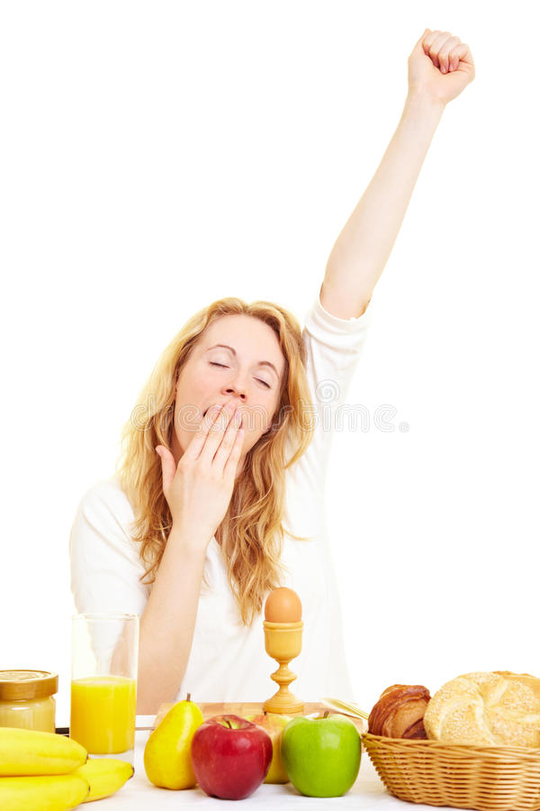 Yawning at breakfast. Woman yawning in the morning on the breakfast table royalty free stock photography