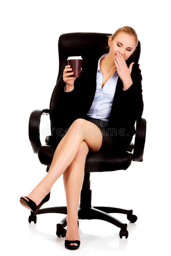 Yawning business woman sitting on wheel chair and holding cup of coffee.  royalty free stock photos