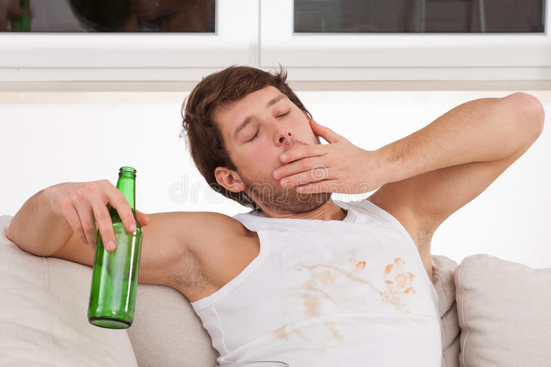 Yawning man with beer. A man in a dirty top yawning holding a bottle of beer stock photography