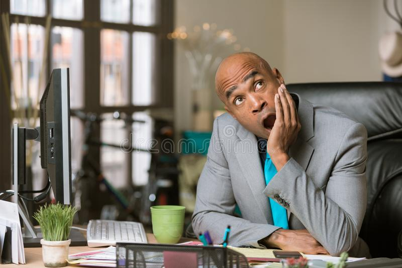 Yawming Man in a His Office. Yawning professional man in his office wearing a blue necktie and green mug royalty free stock photo