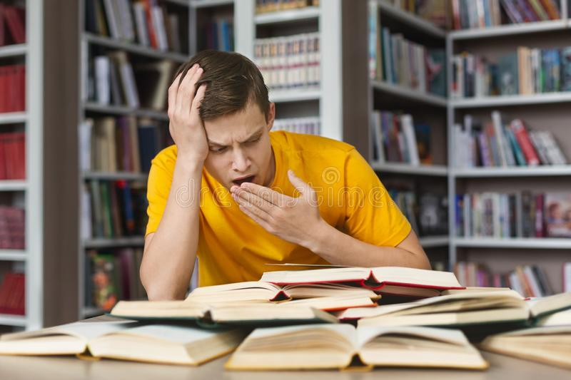 Yawning student sitting in front of books in library. Yawning caucasian student sitting in front of open books, making homework in library stock images