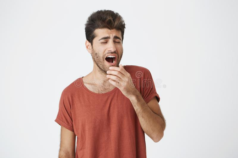 Yawning young fellow with beard and trendy hairstyle tired of work and holding his hand behind his mouth. Student royalty free stock images