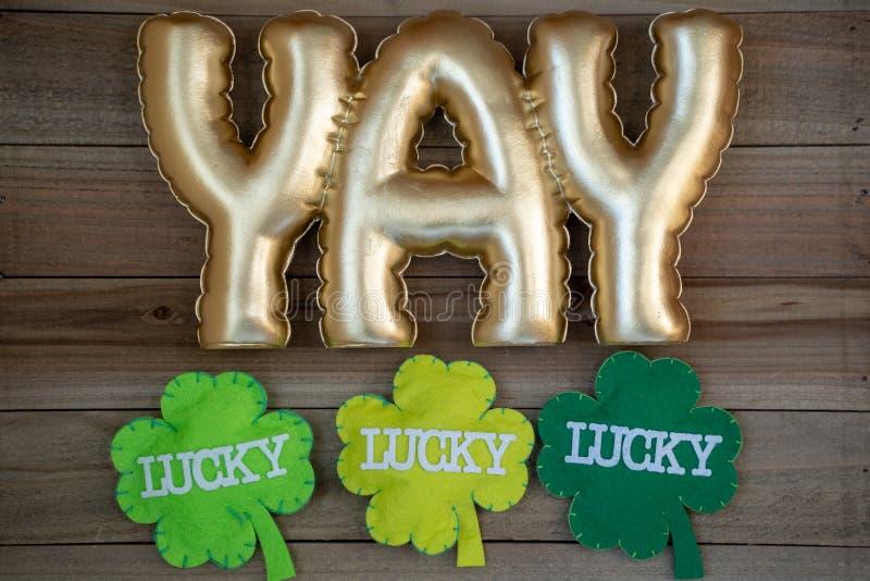 YAY-Goldbeschriftungswort mit glücklichen Shamrocks, Konzept für Tag St. Patricks im März Flatlay auf hölzernem Hintergrund stockfoto