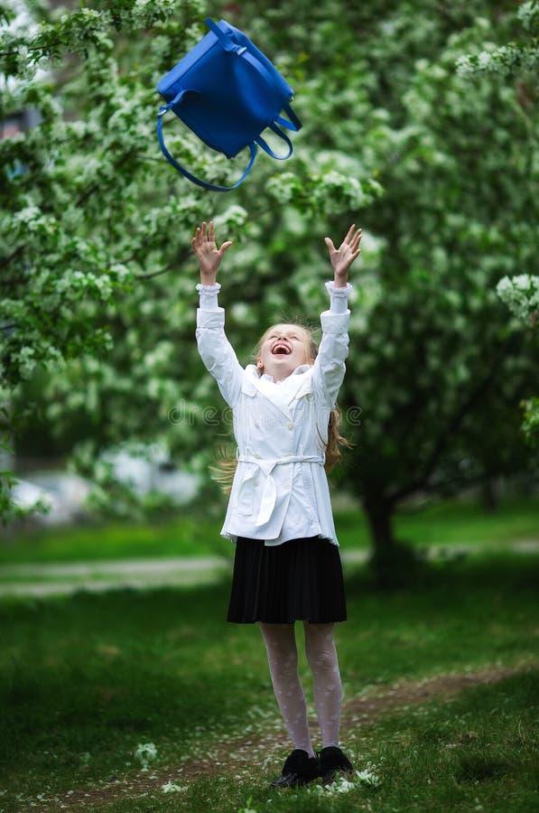 Yay, vacanza! La ragazza felice in uniforme scolastico allegramente getta sulla borsa di scuola Il concetto di istruzione prescol immagine stock libera da diritti