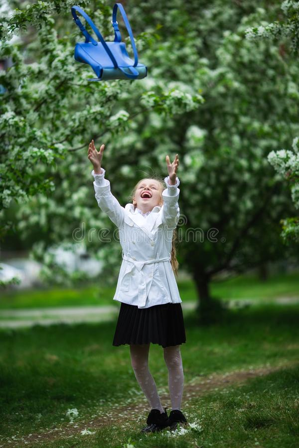 Yay, vacation! Happy girl in school uniform cheerfully throws up school bag. The concept of pre-school education stock photos
