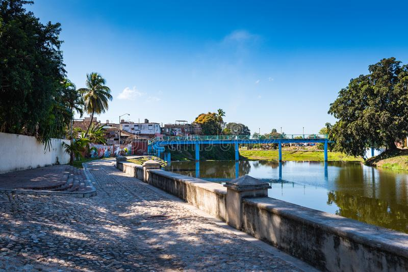 Yayabo River Walkway and Mural. Sancti Spiritus , Cuba / March 15, 2017: Cobblestone walkway and mural along the Yayabo River stock photos