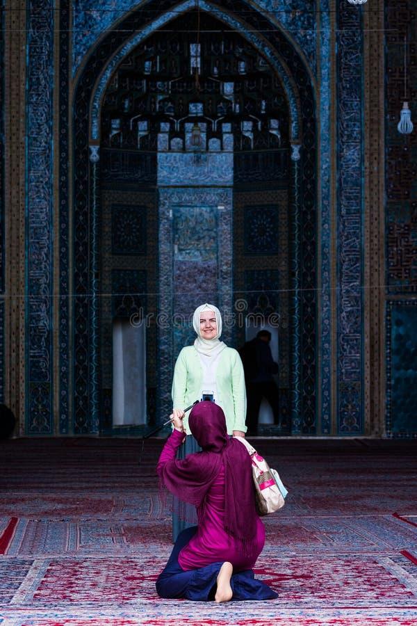 Yazd, Ir? - 17 de maio de 2017 Mulheres no hijab que faz a foto na cidade do deserto na mesquita azul Jama Masjid imagens de stock