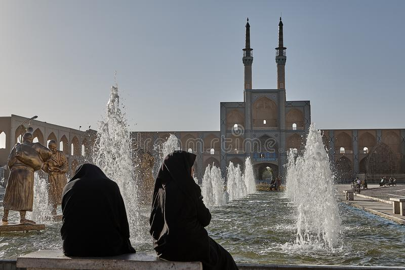Two women wearing the Islamic veil admire the fountain, Iran. stock photos