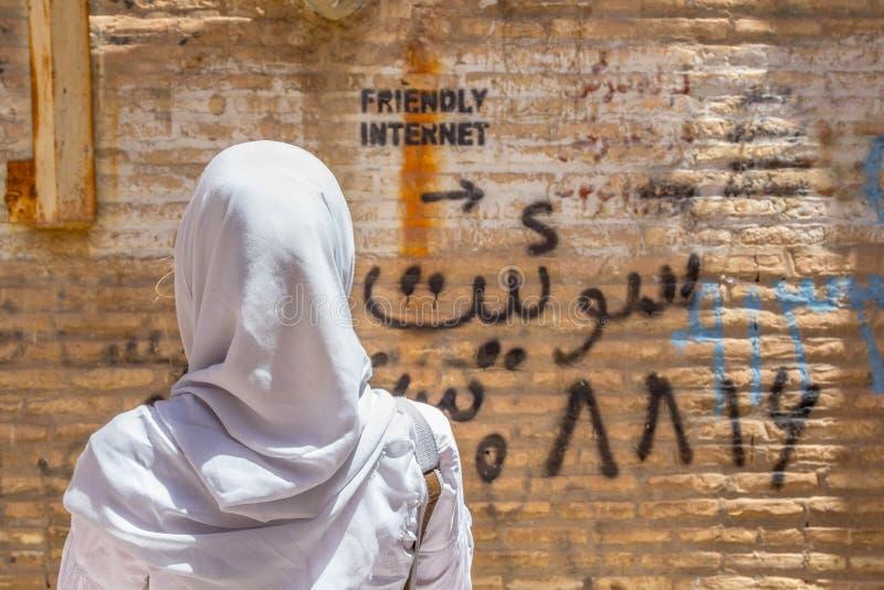 YAZD IRAN - AUGUSTI 18, 2016: Beslöjad kvinna som ser en inskrift på väggen som indikerar den ocensurerade internetfläcken royaltyfri foto