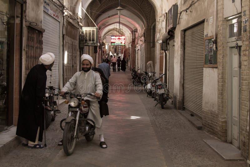 YAZD, IRAN - AUGUSTUS 18, 2016: Iraanse Imams die traditionele kleren dragen die terwijl op een motor in een behandelde straat va royalty-vrije stock foto's