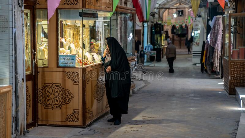 Iranian woman looking at gold accessories and jewelry in grand bazzar of Yazd, Iran royalty free stock photos