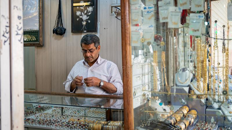 Man repearing an bracelet inside gold accessories and jewelry shop in grand bazzar of Yazd, Iran royalty free stock photo