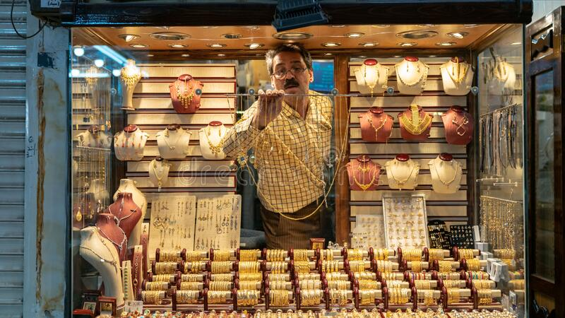 Man working inside the window display of gold accessories and jewelry shop in grand bazzar of Yazd, Iran royalty free stock image