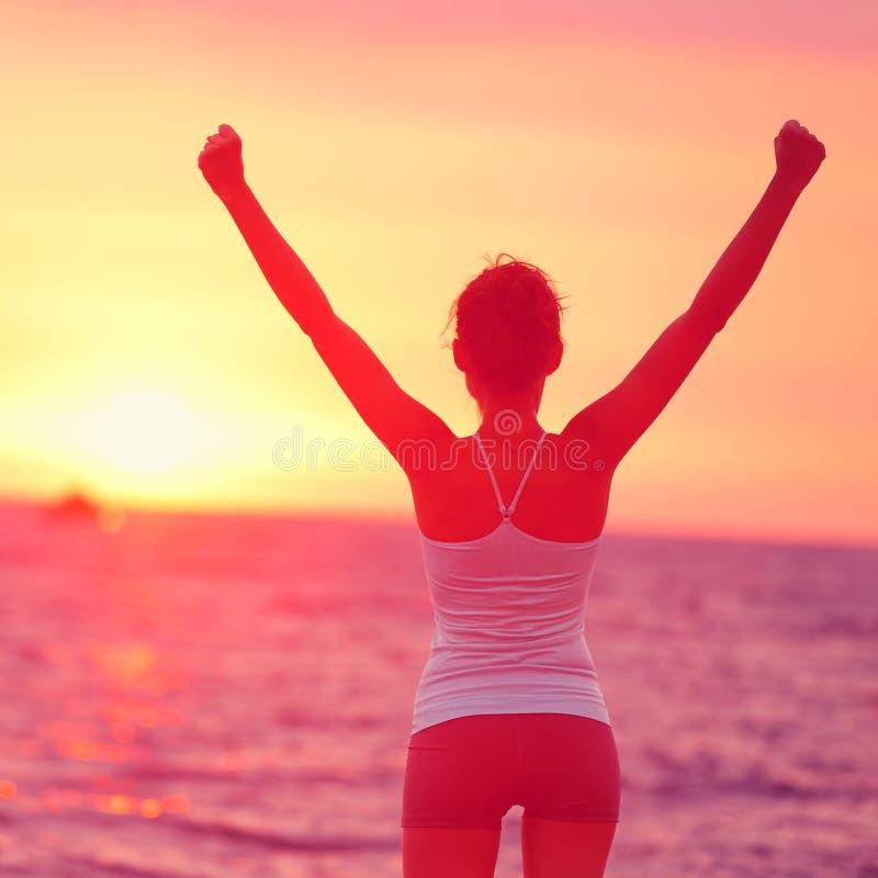 Życia osiągnięcie - szczęśliwe kobiet ręki up w sukcesie zdjęcia stock