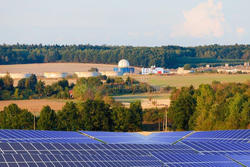 Życiorys benzynowa roślina i energetyczni panel słoneczny na polu zdjęcia royalty free