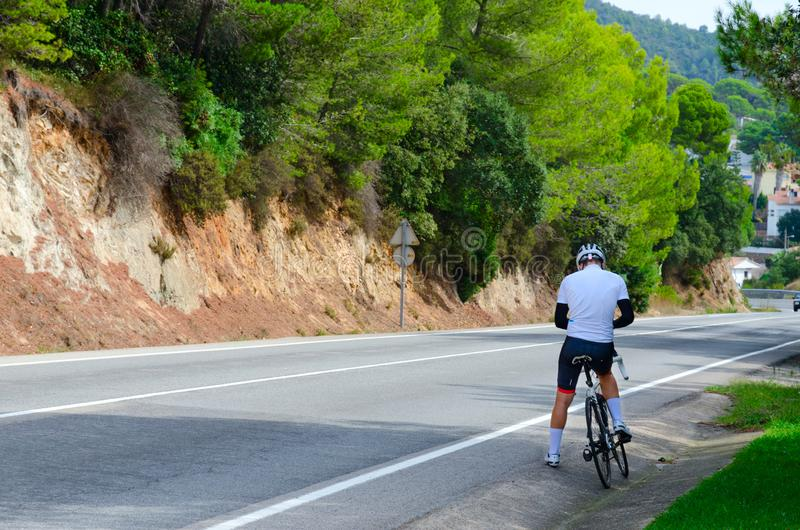YCyclist is on side of road leading from Lloret de Mar to Tossa de Mar, Costa Brava, Catalonia, Spain royalty free stock image