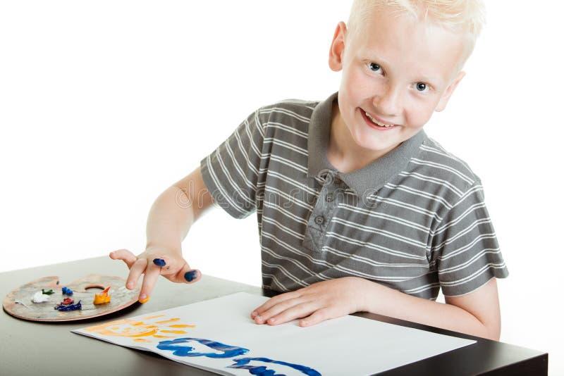 Życzliwa chłopiec robi palcowemu obrazowi obrazy stock