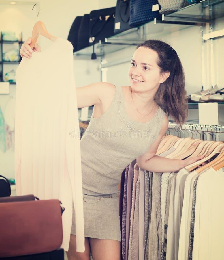 Życzliwa kobieta wybiera nową bluzkę w odzież sklepie zdjęcie royalty free