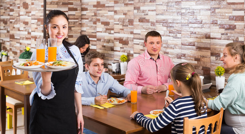 Życzliwa młoda kelnerka wita ciebie rodzinna kawiarnia fotografia stock