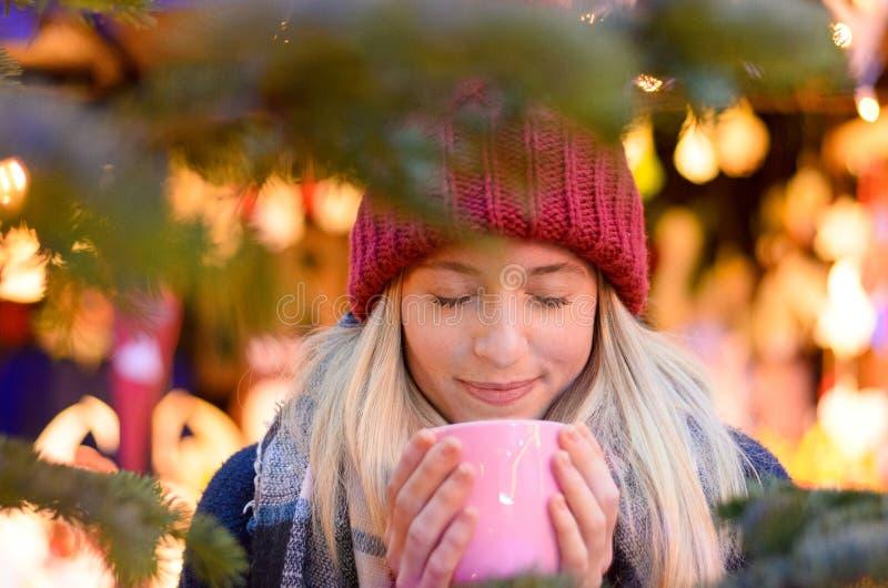 Życzliwa młoda kobieta cieszy się gorącego napój obraz stock
