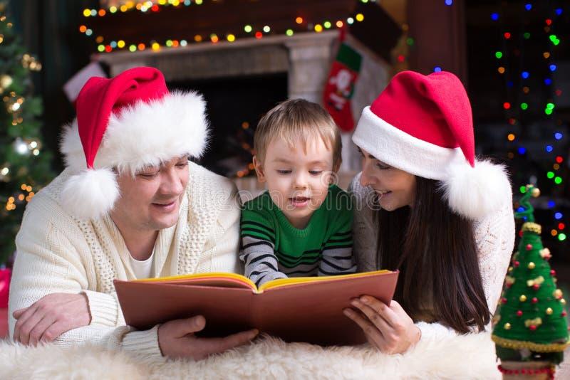 Życzliwa rodzinna czytelnicza książka na Bożenarodzeniowym wieczór fotografia stock