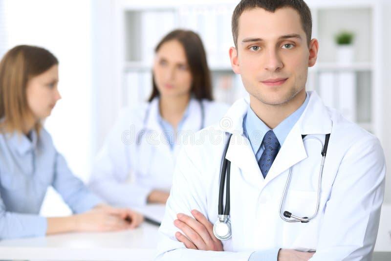 Życzliwa samiec lekarka na tle z pacjentem i jej lekarzem w szpitalnym biurze obraz stock
