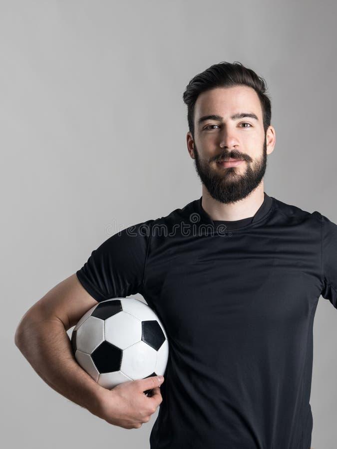 Życzliwa uśmiechnięta brodata gracza piłki nożnej mienia piłka pod jego ręką patrzeje kamerę fotografia royalty free