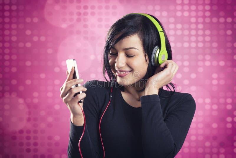 Życzliwa uśmiechnięta dziewczyna słucha muzyka z słuchawkami obrazy royalty free