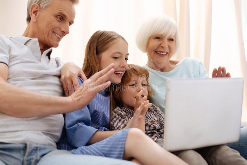 Życzliwi mądrze dzieci używa laptop dla dzwonić wychowywają obrazy stock