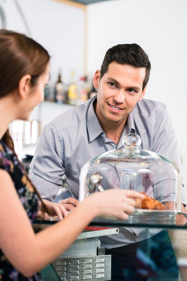 Życzliwy kelner oferuje młodego żeńskiego klienta świeży francuz c fotografia stock