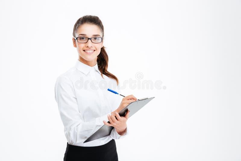 Życzliwy młody uśmiechnięty bizneswoman z schowkiem i piórem fotografia royalty free