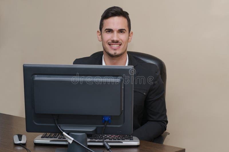 Życzliwy, uśmiechnięty młody biznesmena obsiadanie przy biurkiem, zdjęcie royalty free
