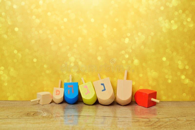 Żydowski wakacyjny Hanukkah tło z przędzalnianego wierzchołka dreidel nad złocistym bokeh Odbitkowa przestrzeń dla teksta zdjęcie royalty free