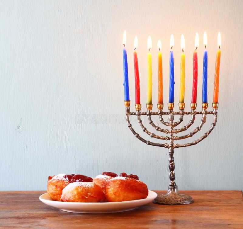 Żydowski wakacyjny Hanukkah z menorah, pączki nad drewnianym stołem retro filtrujący wizerunek fotografia stock