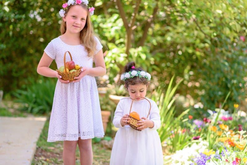 ?ydowski wakacyjny Shavuot HarvestTwo ma?e dziewczynki w biel sukni trzymaj? kosz z ?wie?? owoc w lato ogr?dzie fotografia stock