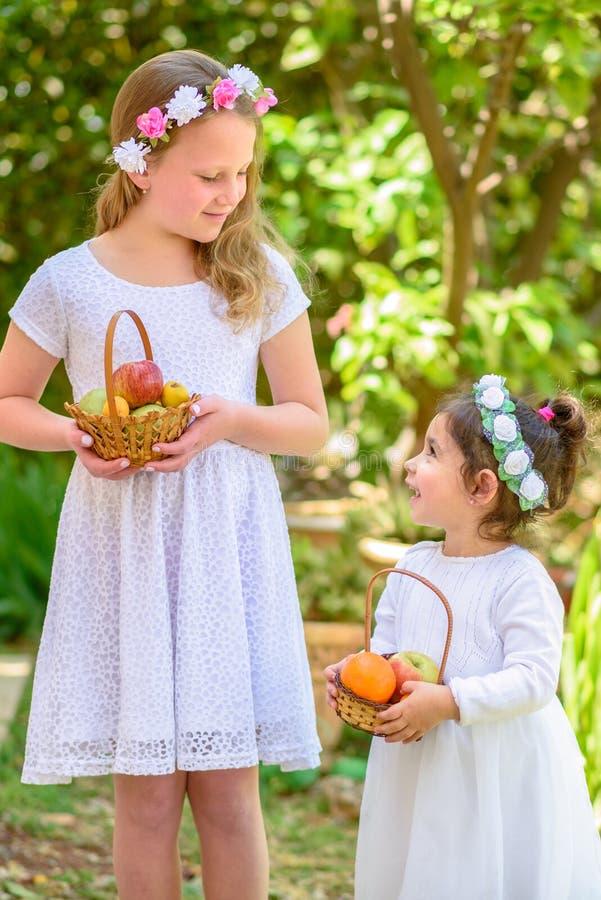 ?ydowski wakacyjny Shavuot HarvestTwo ma?e dziewczynki w biel sukni trzymaj? kosz z ?wie?? owoc w lato ogr?dzie obrazy royalty free