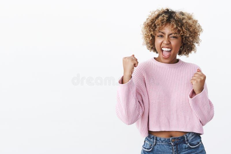 Yeah beb? n?s fizemo-lo Triunfando a mulher afro-americano bonita deleitada e alegre que grita da alegria e da felicidade fotos de stock royalty free