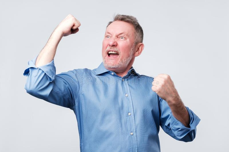 Happy senior strong man, raising clenched fists in hooray gesture, triumphing stock images